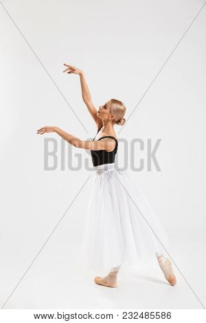 Photo of amazing pretty young woman ballerina dancing gracefully over white wall background isolated. Looking aside.