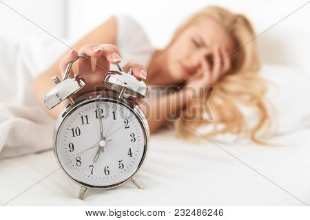 Close up of a sleepy young woman turning alarm off in the morning while lying in bed