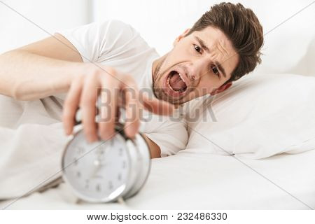 Close up of a screaming young man turning alarm off in the morning while lying in bed
