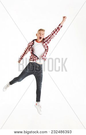 Full length portrait of cheerful youngster wearing plaid shirt yelling and acting like superhero lifting hand up isolated over white background