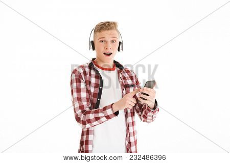 Modern youngster in casual t-shirt 17y wearing braces listening to favorite music via wireless earphones and using smartphone isolated over white background