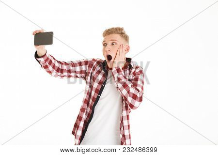 Young guy with braces taking selfie on mobile phone and expressing shock or surprise isolated over white background