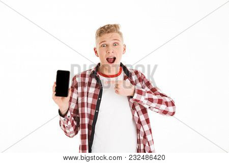 Portrait of a surprised schoolboy pointing finger at blank screen mobile phone isolated over white background