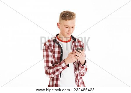 Caucasian teenager in casual t-shirt 17y wearing braces holding mobile phone and looking at screen while chatting isolated over white background