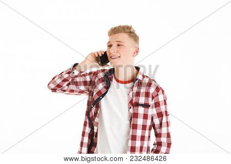 Youngster in casual t-shirt 17y wearing braces holding smartphone in hand and having pleasant mobile conversation isolated over white background