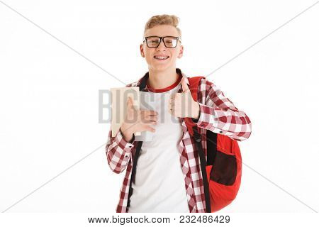 Portrait of a happy schoolboy in eyeglasses with backpack holding books and showing thumbs up gesture isolated over white background