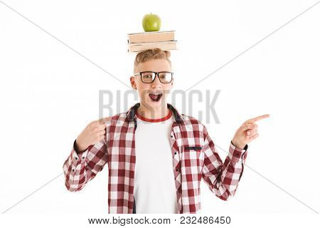 Portrait of a joyful schoolboy in eyeglasses holding stack of books and green apple on his head and pointing fingers away at copy space isolated over white background