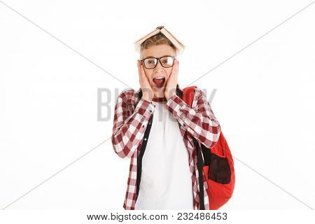 Portrait of an excited schoolboy in eyeglasses with backpack holding book on his head isolated over white background