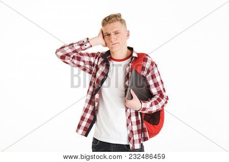 Portrait of caucasian teenage boy wearing plaid shirt expressing confusion or problem on face and holding silver laptop isolated over white background