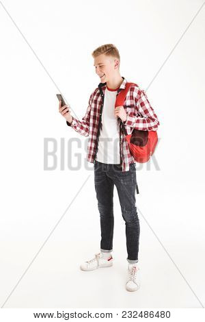 Full length portrait of a happy schoolboy in eyeglasses with backpack using mobile phone isolated over white background