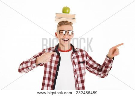 Portrait of an excited schoolboy in eyeglasses holding stack of books and green apple on his head and pointing fingers away at copy space isolated over white background