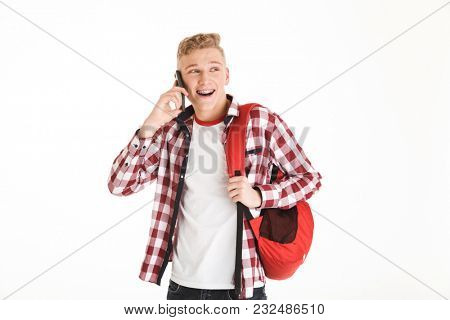 Image of cheerful hipster guy 18y wearing plaid shirt and backpack talking on mobile phone with smile isolated over white background