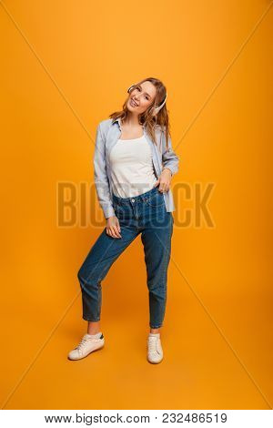 Image of smiling young lady standing listening music isolated over yellow background. Looking camera.
