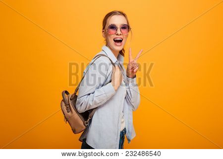 Image of smiling young lady standing isolated over yellow background. Looking camera with peace gesture.