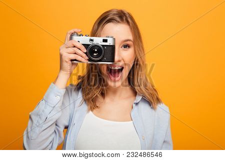 Close up portrait of a happy young girl with braces taking a picture with photo camera isolated over yellow background