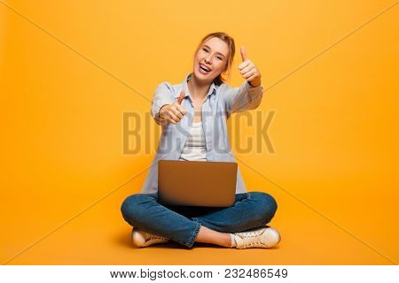 Image of smiling young lady student sitting isolated over yellow background. Looking camera using laptop computer showing thumbs up.