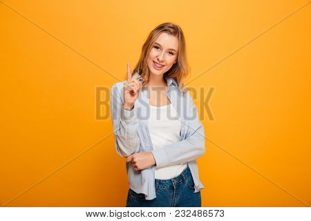 Portrait of lovely woman with auburn hair pointing index finger up on copyspace text or product isolated over yellow background