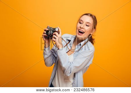 Portrait of a cheerful young girl with braces holding photo camera and looking away isolated over yellow background