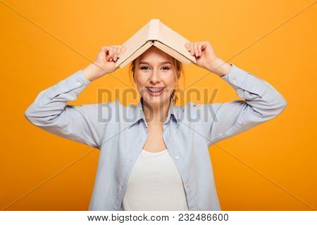 Image of cheerful young lady student standing isolated over yellow background holding book. Looking camera.