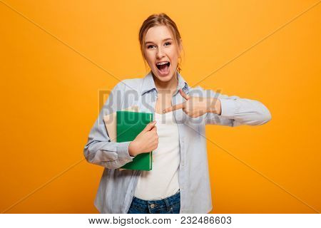 Photo of excited young woman student standing isolated over yellow background. Looking camera pointing holding books.