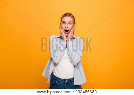 Portrait of a surprised young girl with braces looking at camera isolated over yellow background