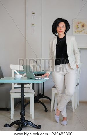 Business Lady Dressed In White Suit Working On A Laptop
