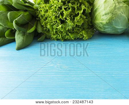 Green Vegetables. Green Vegetable On Blue Wooden Background. Spinach, Cabbage And Lettuce. Top View.