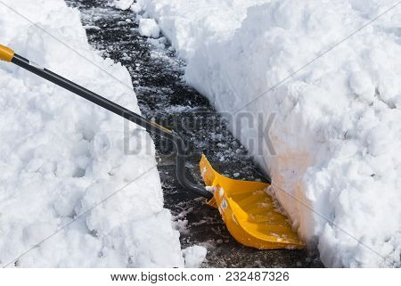 A Yellow Snow Shovel Resting On A Black Driveway With Over One Foot Of Snow Surrounding It.