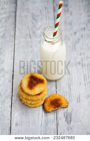 Bottles Of Milk With Red Striped Straws And Chip Cookies On Grey Wooden Background