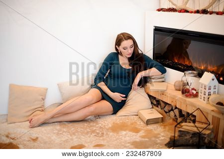Beautiful Young Pregnant Woman In A Blue Dress Lying On The Carpet Near The Fireplace