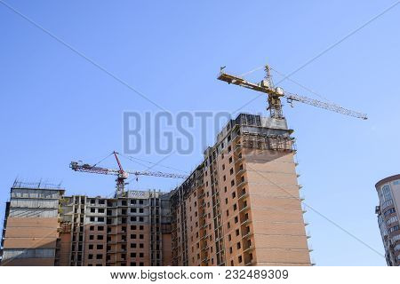 Construction Of A New House. Tower Building Crane Against The Blue Sky And Sun. Construction Of New