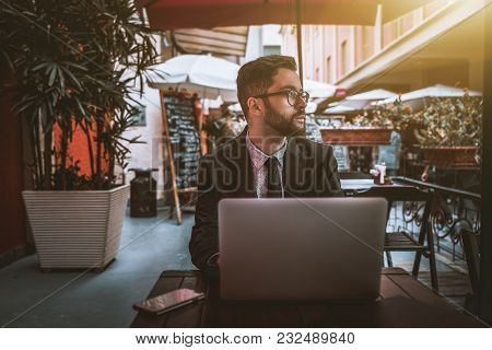 Young Diffident Bearded Businessman In The Glasses And A Formal Suit Is Sitting With The Laptop In A