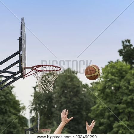 Street Basketball Game. Basketball Shield, Basket And Ball On Background Of Sky, Trees, Street In Su