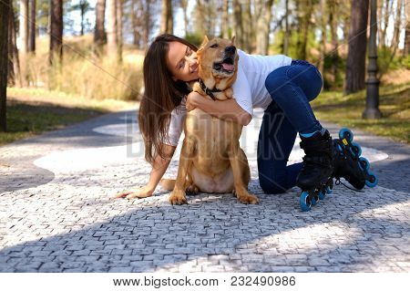 Brunette Casual Female Having Fun With Her Brown Pitbull Dog In A Park.