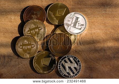 Crypto Coins With  Light From The Side On Wooden (table) Background.  Metal Coins  Of Cryptocurrency