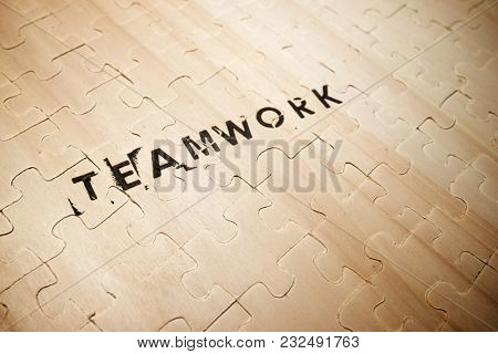 Teamwork word stamped on a wooden puzzle.