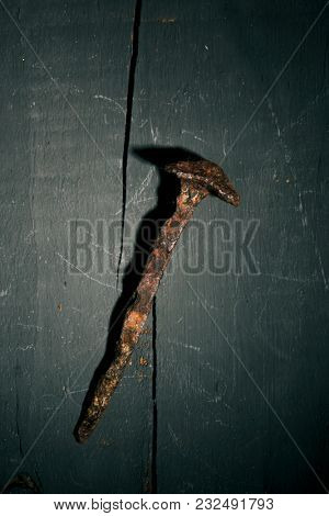high angle view of a rusty nail, depicting one of the nails of the holy cross, on a rustic wooden surface, with a dramatic effect