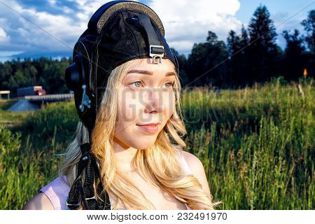 Girl Pilot In A Black Flight Helmet Is In The Summer On A Background Of Green Grass In Sunny Day