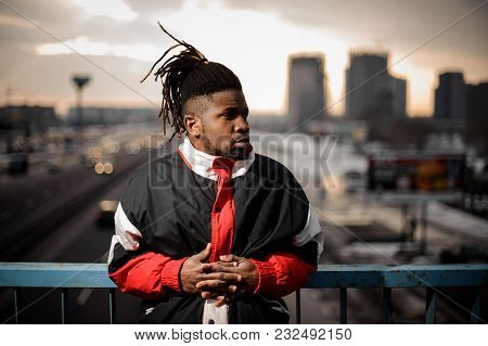Afro-american Man With Dreadlocks Dressed In Sportswear Standing On The Background Of The City Road