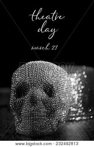 closeup of a sparkly skull and and a sparkly top hat, and the text theatre day march 27 against a black background