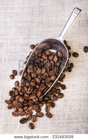Close-up Of Roasted Black Coffee In Beans On The Light-colored Rough Background