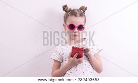 A Girl In Pink Glasses Uses A Red Smartphone. Portrait.