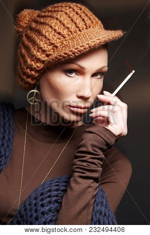 Portrait Of Woman With Cigarette In Brown Clothing And Winter Hat. Isolated On Brown Background
