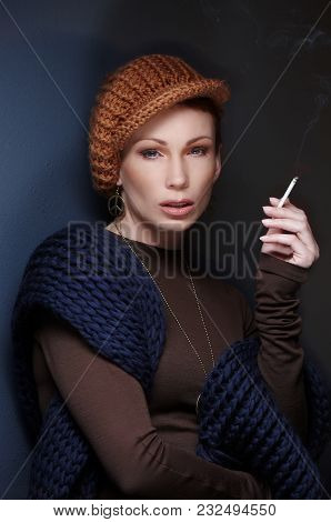 Portrait Of Woman With Cigarette In Brown Winter Head And Blue Scarf.