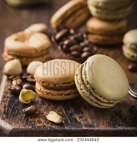 French Coffee And Pistachio Macarons With Ganache Filling With Coffee Beans On Old Wooden Board On R