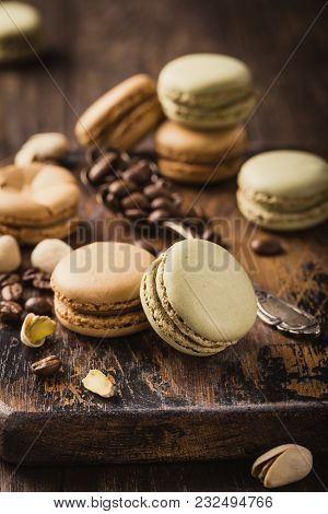 French Coffee And Pistachio Macaroons With Ganache Filling With Coffee Beans On Old Wooden Board On