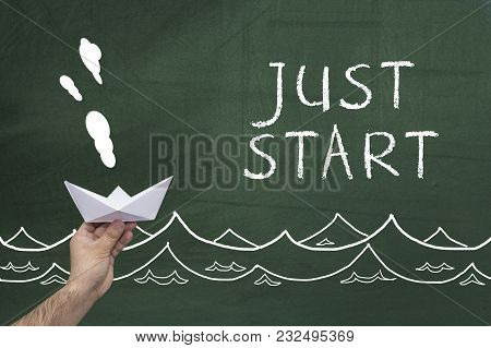 Hand Holding Paper Ship Against Chalkboard With Words: Just Start.