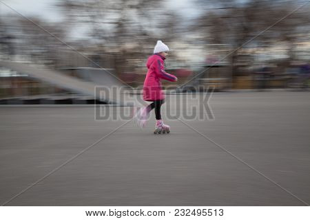 Little Girl Is Rollerblading. She Is Looking Away.
