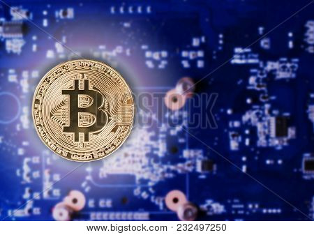 Physical Gold Bitcoin Coin On A Computer Video Card. New Independent Worldwide Cryptocurrency. Bitco
