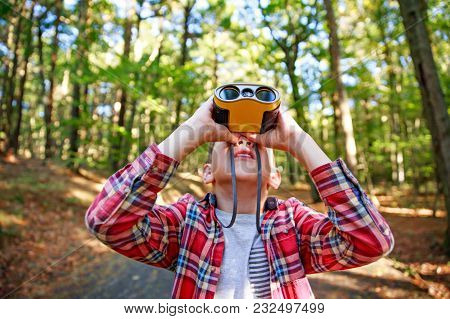 Boy Looks Up Through Binoculars. The Child Watches Something In The Sky.